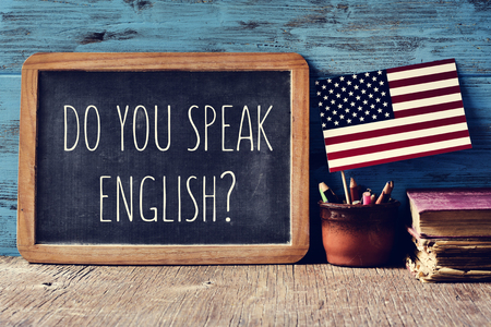 a chalkboard with the question do you speak English? written in it, a pot with pencils and the flag of the United States, on a wooden desk