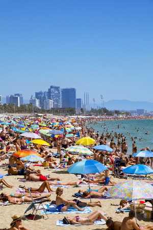 frequented: Barcelona, Spain - July 10, 2016: People sunbathing at Platja del Bogatell beach in Barcelona, Spain. This busy beach is mainly frequented by the locals