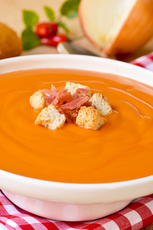andalusian cuisine: closeup of a bowl with spanish salmorejo cordobes or porra antequerana, topped with serrano ham and croutons, on a set table