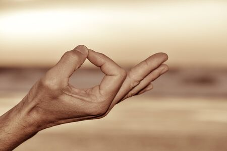 yogi aura: closeup of a young man meditating with his hands in gyan mudra outdoors