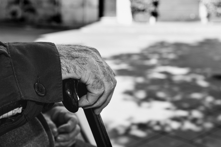 gerontology: closeup of the hand of an old caucasian man with a walking stick, in black and white