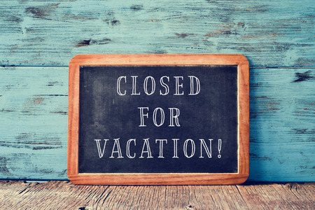 a wooden-framed chalkboard with the text closed for vacation written in it, on a rustic wooden surface, against a blue wooden background Stockfoto