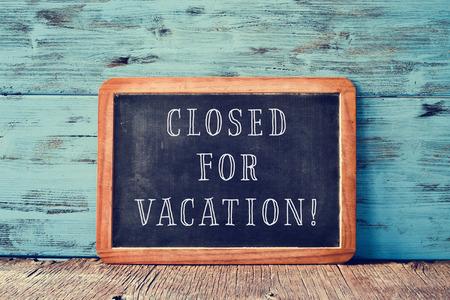 una pizarra con marco de madera con el texto cerrado por vacaciones escrito en él, sobre una superficie de madera rústica, sobre un fondo de madera azul Foto de archivo