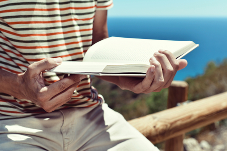 prose: closeup of a young caucasian man reading a book outdoors, with the ocean in the background Stock Photo
