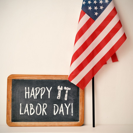 joblessness: a wooden-framed chalkboard with the text happy labor day written in it and a flag of the United States, against an off-white background