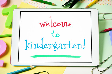 welcome desk: closeup of a tablet computer with the text welcome to kindergarten in its screen, on a desk full of numbers, pencil crayons of different colors and other stationery