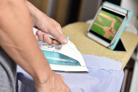 soltería: Primer plano de un hombre joven que plancha una camisa rayada con una plancha eléctrica en una tabla de planchar, mientras ve un partido de béisbol en línea en su computadora de la tableta