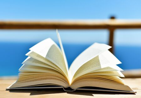 prose: closeup of an open book on a wooden table outdoors, with the ocean in the background