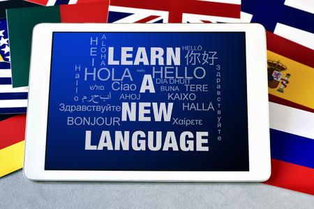 courses: the text learn a new language and the word hello in different languages in the screen of a tablet computer, surrounded by flags of different countries