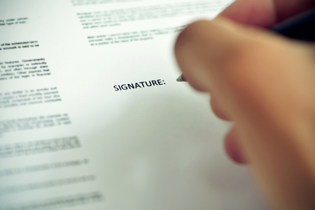 signer: closeup of a young caucasian man about to sign a document with a pen under the word signature