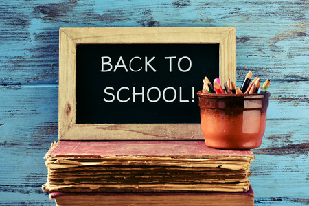 beginning school year: a chalkboard with the text back to school written in it and a pot with some pencils on a pile of old books, against a rustic blue wooden background Stock Photo
