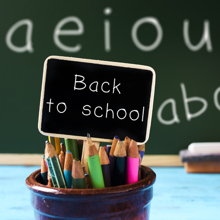 beginning school year: closeup of a black signboard with the text back to school placed in a pot full of pencil crayons of different colors, and a chalkboard with the vowels handwritten in it in the background