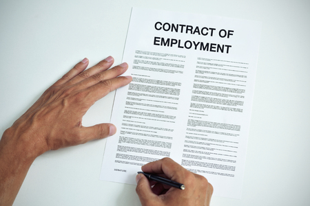 signer: closeup of a young caucasian man about to sign a contract of employment