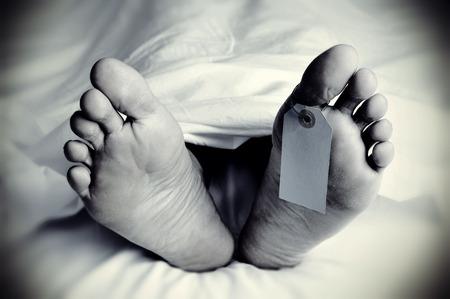 Gros plan sur les pieds d'un cadavre recouvert d'une feuille, avec une étiquette vierge attaché sur le gros orteil de son pied gauche, en noir et blanc, avec une vignette ajouté Banque d'images - 63769478