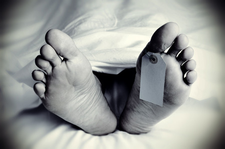 closeup of the feet of a dead body covered with a sheet, with a blank tag tied on the big toe of his left foot, in monochrome, with a vignette added