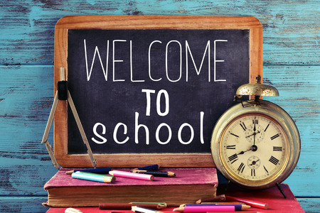 beginning school year: a chalkboard with the text welcome to school, some old books, an old clock, a compass and some pencil crayons of different colors, against a blue wooden background Stock Photo