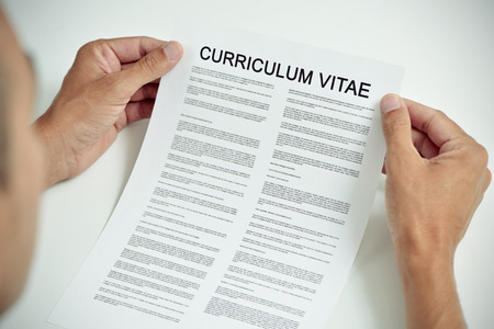 vitae: closeup of a young caucasian man sitting at an office desk with a curriculum vitae in his hands