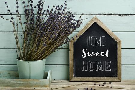 primo piano di una lavagna a forma di casa con la casa di testo dolce casa scritto in esso e un mazzo di fiori di lavanda in un vaso di fiori, su uno sfondo blu pallido, rustico Archivio Fotografico
