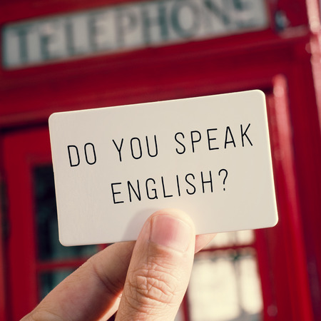 british english: a man holding a signboard with the text do you speak english? with a typical british red telephone booth in the background Stock Photo