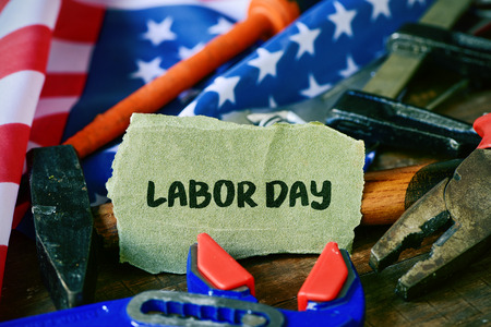 joblessness: closeup of a piece of sandpaper with the text labor day written in it, a pile of different tools and a flag of the United States in the background Stock Photo