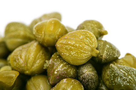 closeup of a pile of pickled capers, against a white background