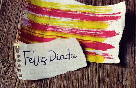 el texto Felic Diada, Día Nacional de Cataluña feliz en catalán escrito en un pedazo de papel, y la bandera catalán pintado en otra hoja de papel, en una superficie de madera rústica