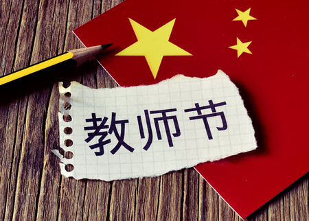 literacy instruction: closeup of a peace of paper with the text Teachers Day written in Chinese, a pencil and the flag of China, placed on a rustic wooden surface Stock Photo