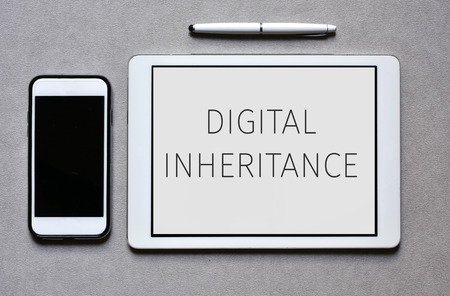 inheritance: high-angle shot of a smartphone, a tablet computer with the text digital inheritance in its screen, and a digital pen on an elegant gray surface Stock Photo