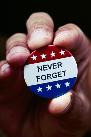 closeup of a the hand of a young caucasian man showing a pin button with the text never forget and the colors and stars of the flag of the United States