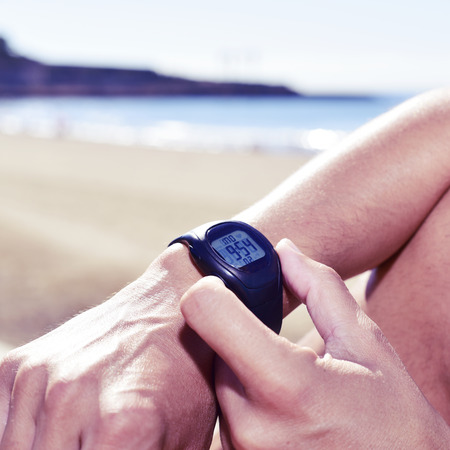 syncing: closeup of a young sportsman syncing his smartwatch, with the sea in the background