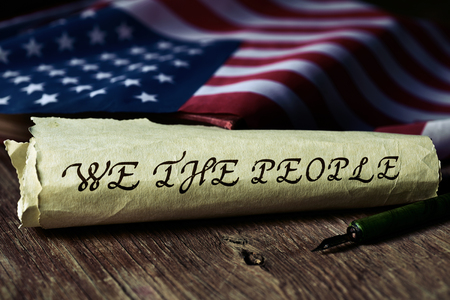 we the people: the text we the people, the first words of the United States Constitution, written with a dip pen in a yellowish piece of paper and the flag of the United States