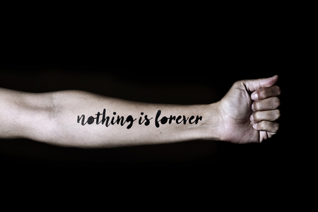 arm tattoo: closeup of a young caucasian man with the text nothing is forever simulating a tattoo in his forearm, against a black background