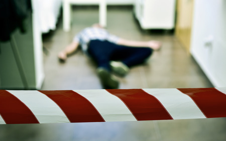 murdered: detail of a crime scene with the dead body of a young man lying in the floor indoors, with a red and white police tape in the foreground