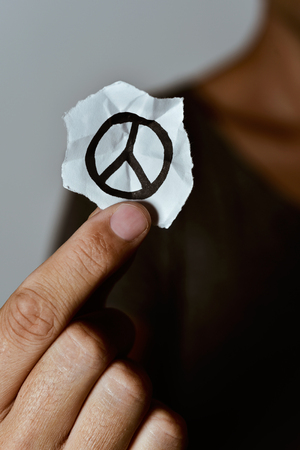 non violence: closeup of a young man showing a piece of paper with a peace symbol drawn in it Stock Photo