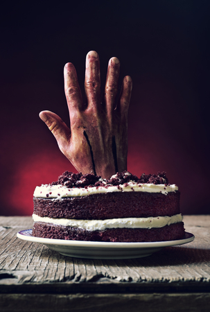 a red velvet cake topped with a bloody hand in a scary scene for halloween, on a rustic wooden table Stock Photo