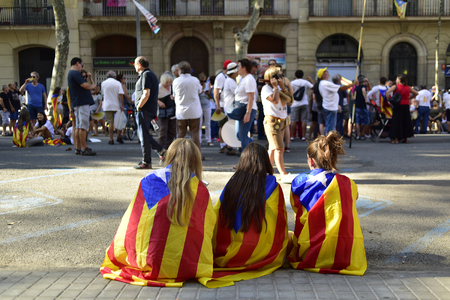 separatist: Barcelona, Spain - September 11, 2016: Girls covered with the separatist flag in a rally in support for the independence of Catalonia in Barcelona, Spain, during its National Day