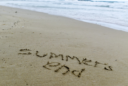 vac: closeup of the text summers end carved in the sand of a beach Stock Photo