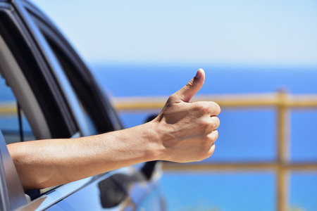 closeup of a young caucasian man giving a thumbs up sign throw the window of a car parked near the ocean