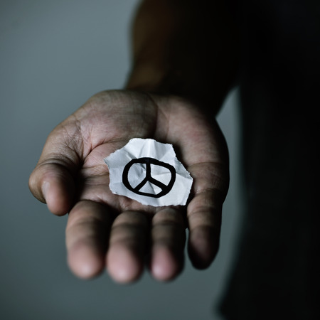ceasefire: closeup of a young man with a piece of paper with a peace symbol drawn in it, in the palm of his hand