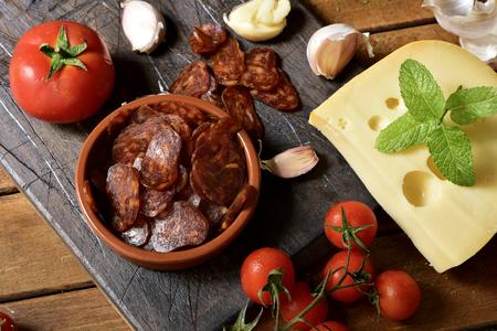 carnes y verduras: de alto ángulo de disparo de un cuenco con unas rodajas de chorizo ??español, una salchicha de cerdo típico de España, en una mesa de madera rústica junto a un trozo de queso, tomates y algunos dientes de ajo