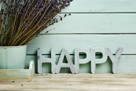 madera rústica: Primer plano de la palabra tridimensional feliz y un montón de flores de lavanda en una maceta, contra un fondo azul pálido rústico