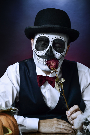 a man with a mexican calaveras makeup, wearing vest, bow tie and bowler hat, smells a dried rose, with a carved pumpkin and a skull in the foreground Stock Photo
