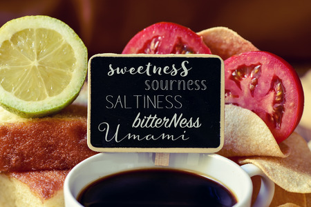 sweetness: closeup of a black chalkboard with the name of different tastes, such as sweetness, sourness, saltiness, bitterness or umami, placed on a pile of some different products representative of this tastes