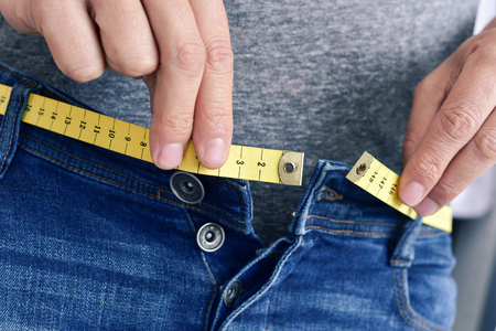 reduce: a young man with a measuring tape as a belt tries to fasten his trousers, because of the weight gain
