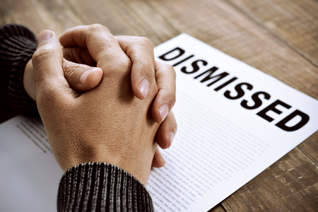 clasped hands: closeup of the clasped hands of a young caucasian man on a document with the text dismissed, placed on a rustic wooden table Stock Photo