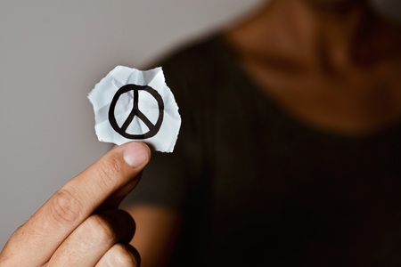 ceasefire: closeup of a young man showing a piece of paper with a peace symbol drawn in it Stock Photo