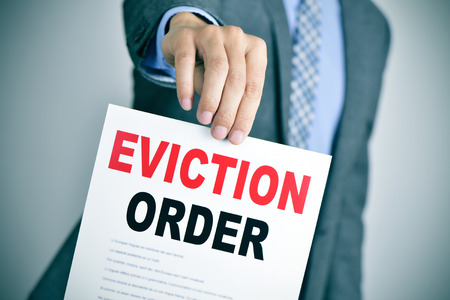 recourse: a young caucasian man wearing a gray suit shows a document with the text eviction order Stock Photo