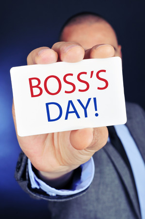headman: a young caucasian businessman shows a signboard with the text boss day written in it Stock Photo