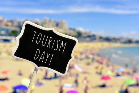 vac: closeup of a black signboard with the text tourism day written in it in front of a blurred crowded beach