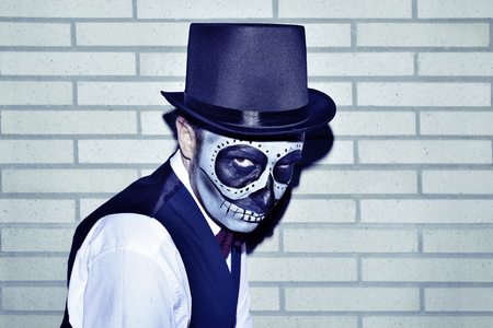 portrait of a man with a mexican calaveras makeup, wearing waistcoat and top hat, against a brick wall